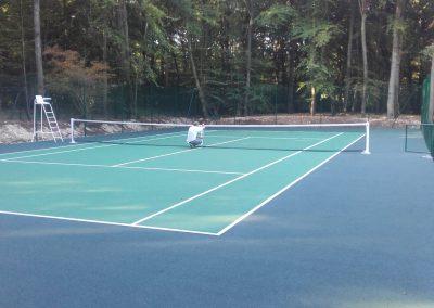Construction d'un court de tennis en béton poreux avec clôture surbaissée à Menilles