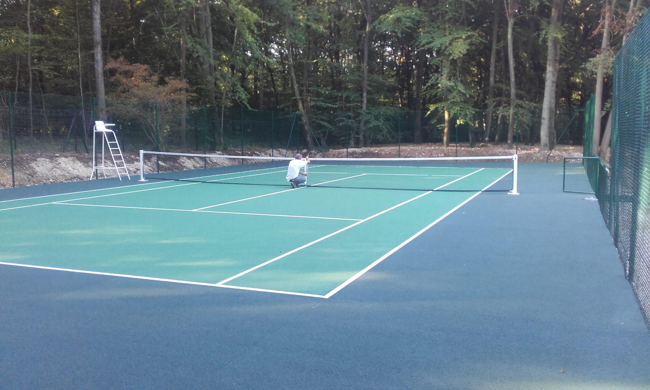 Construction d'un court de tennis en béton poreux avec une partie de côture surbaissée à Menilles